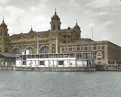 "United States Immigration Station building on Ellis Island. A ferry named ""Laura"" is docked in front of the building. c. 1900"
